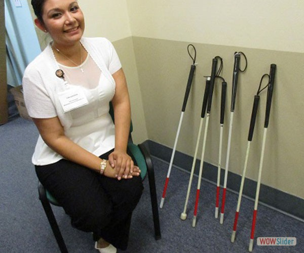 Antonia Quesada sitting next to white mobility canes used for blind children.