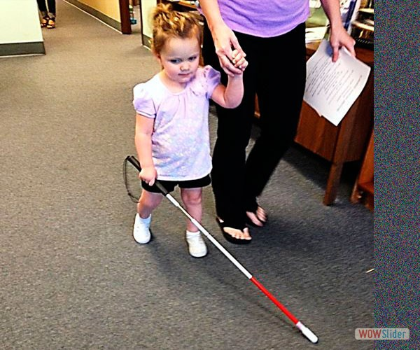 A blind child is learning how to use her white mobility cane in our children's department.